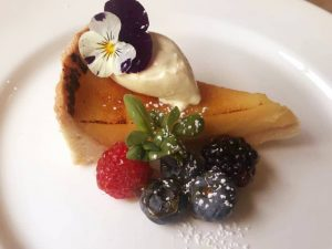 Slice of caramelised lemon tart with clotted cream,and berries at Bel & The Dragon Windsor