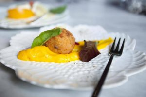 Arancini balls in a delicate white dish served as an amuse bouche at Caldesi in Campagna