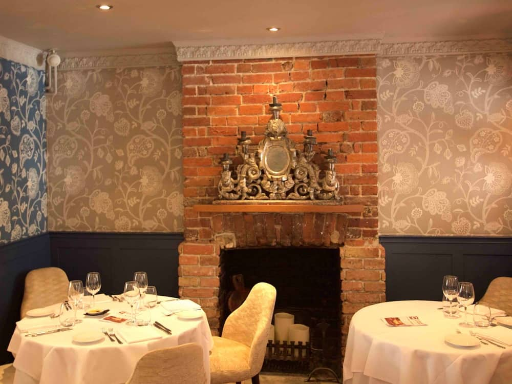 Stunning linen wallpaper, exposed brick fireplace and ornate mantel artwork at Caldesi in Campagna in Bray Berkshire