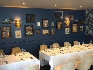 Stylish dark blue wall and eclectic gallery artwork showcasing the memory boxes created by Katie Caldesi at the Bray Restaurant in Berkshire – Caldesi in Campaga