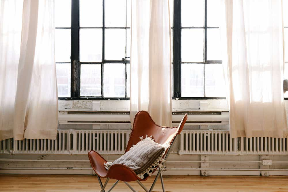 Simple light muslin curtains drape the creol windows with a tan leather butterfly chair