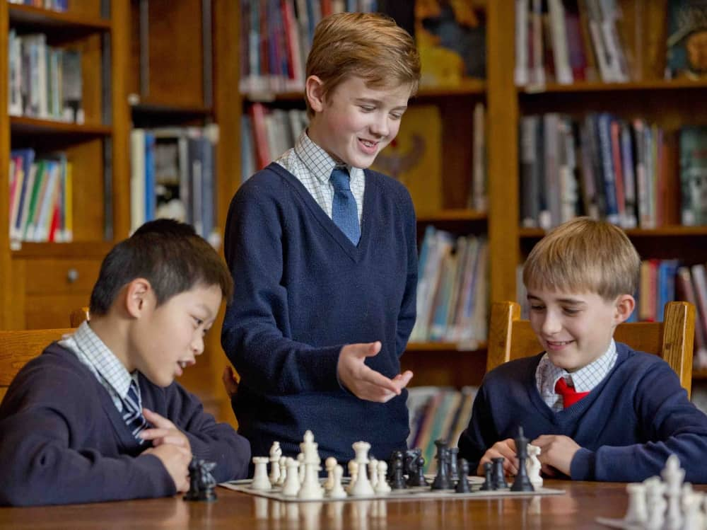 three Horris Hill boys playing chess in the wood panelled library at the Berkshire prep school