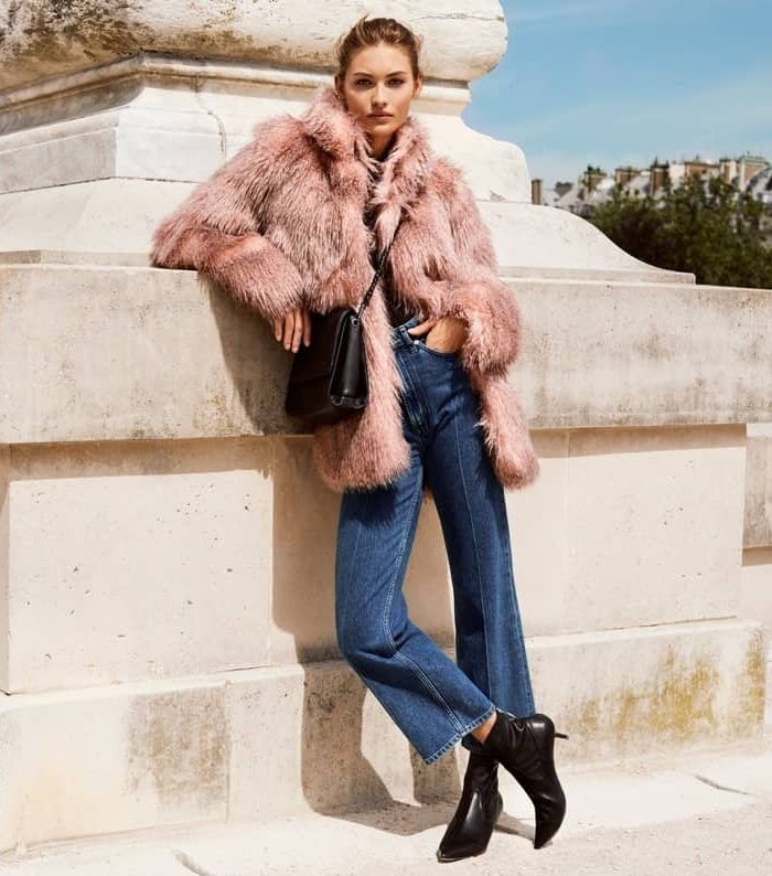 Model wear blush pink H&M faux fur, jeans and black boots while leaning on a stone monument