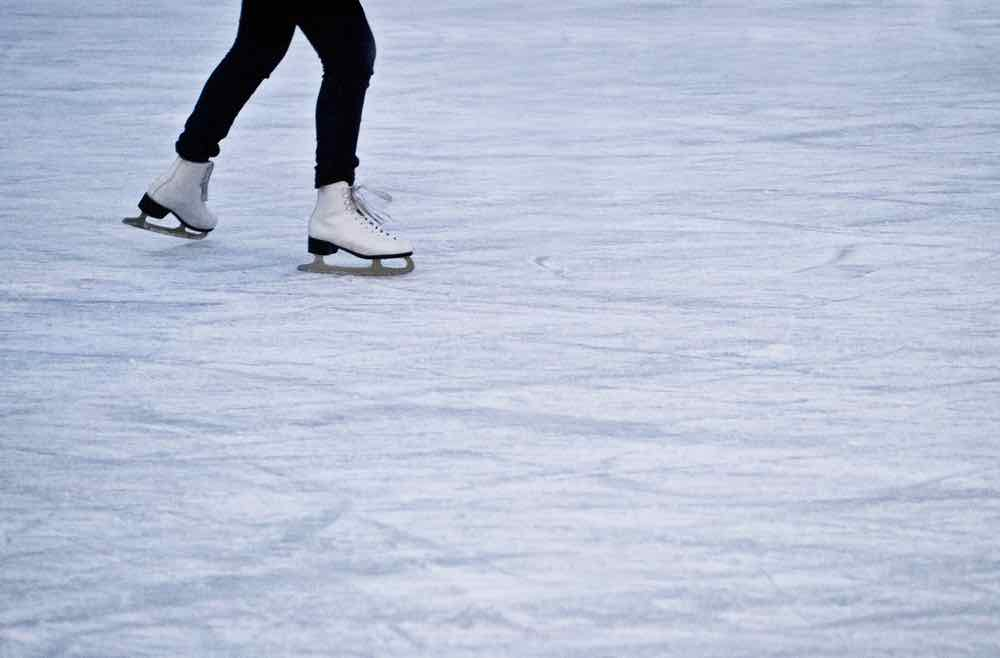 Woman wearing black leggings and white leather skates glide across the ice rink
