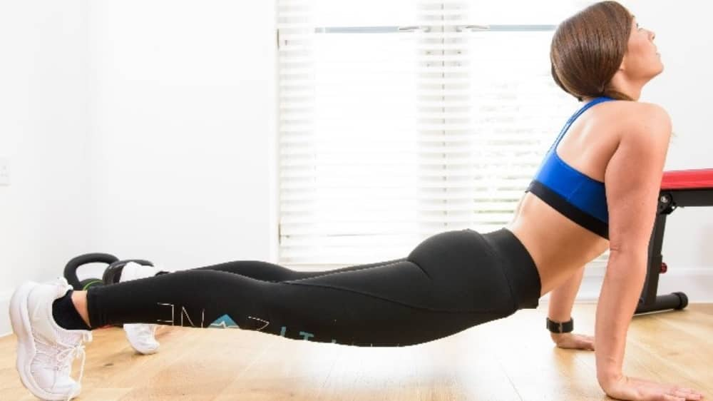Fitness instructor Anna Bella Cousins of MyFitZone stretches in black leggings and blue bra top