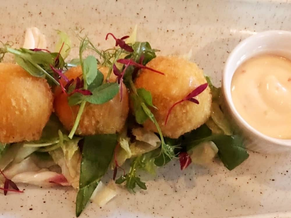 fishcake balls with salad leaves and spiced mayo