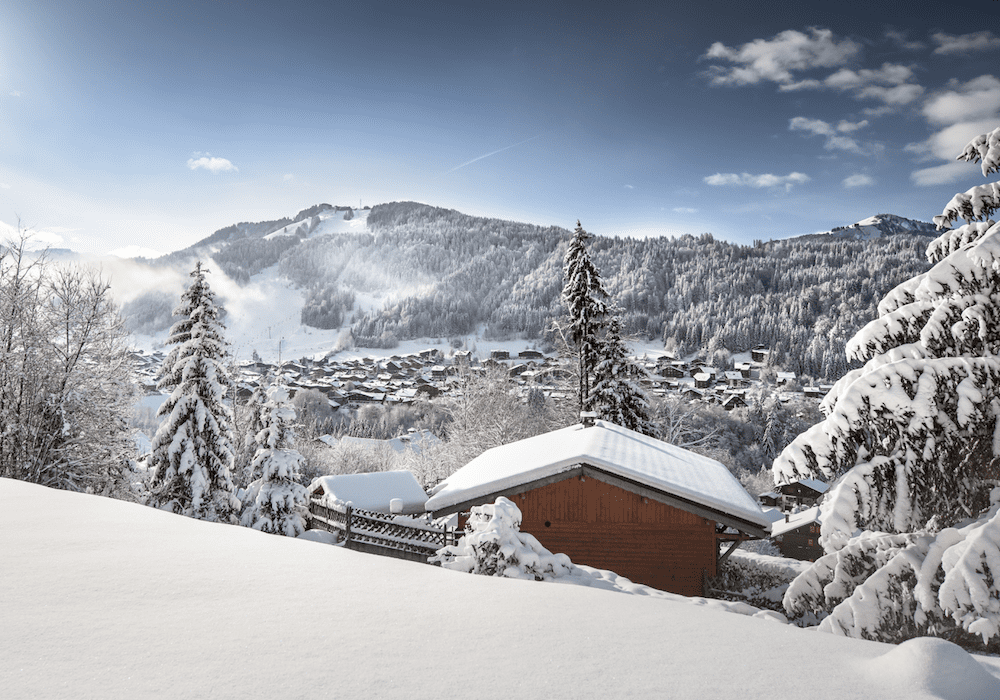 Traditional wooden alpine chalet on the snowy mountains under blue skies and sunshine