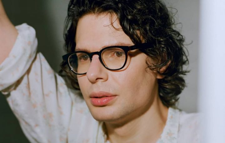 Comedian Simon Amstell wearing a white shirt and black framed specs