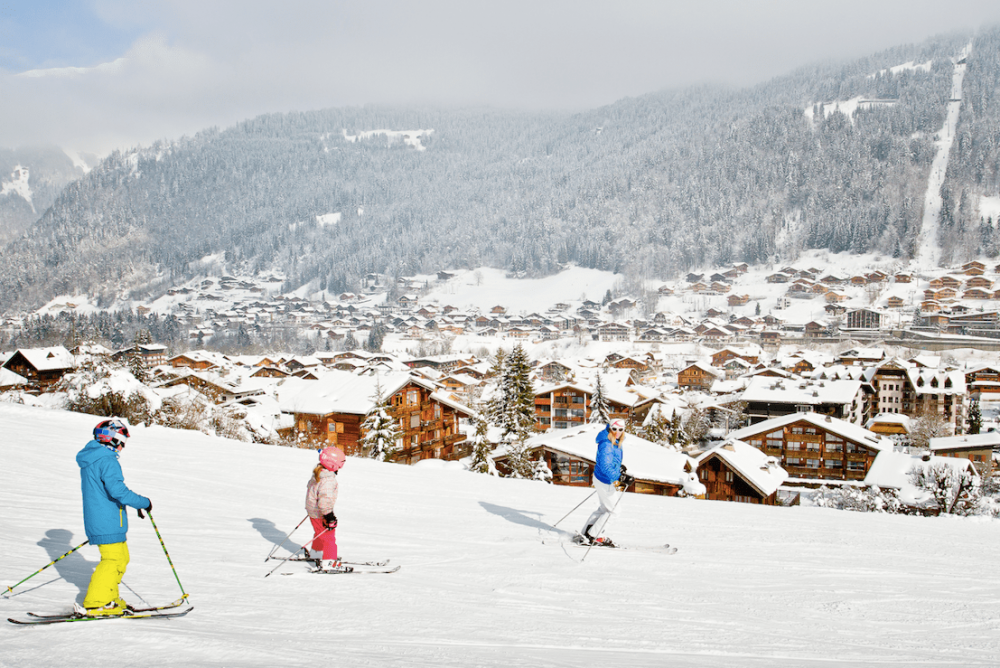 Kids ski down the snowy slopes of Pleney in france