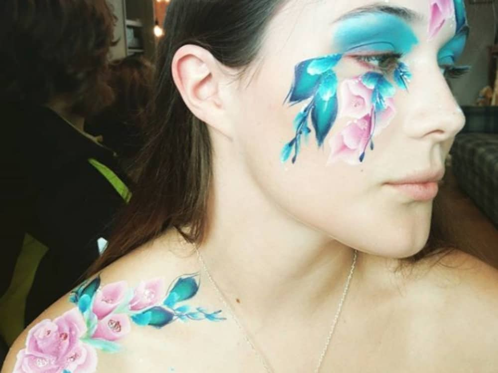 Grown up floral face and body arts with a trail of flowers and leaves down face and arm