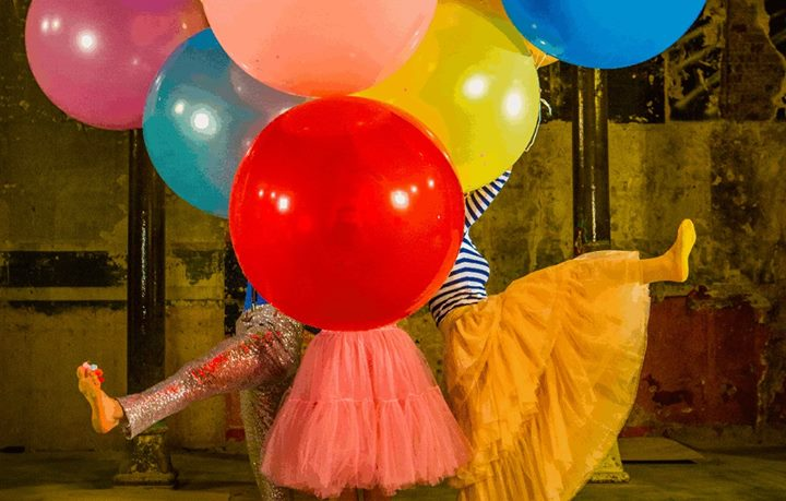 Enormous colourful balloons hide the dancers behind in their ballot skirts and coloured tights