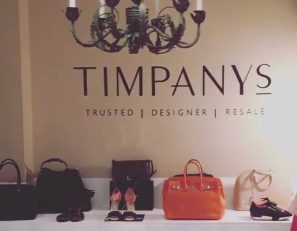 Designer bags and shoes on display under a black chandelier at the Timpany's Pop Up in Sunningdale