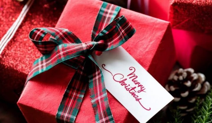 Christmas gifts wrapped in red paper, tartan bows and handwritten tags