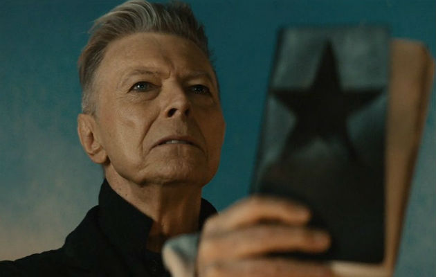 David Bowie holding up a black leather bound book with a star embossed on it for the video of his last album Dark Star