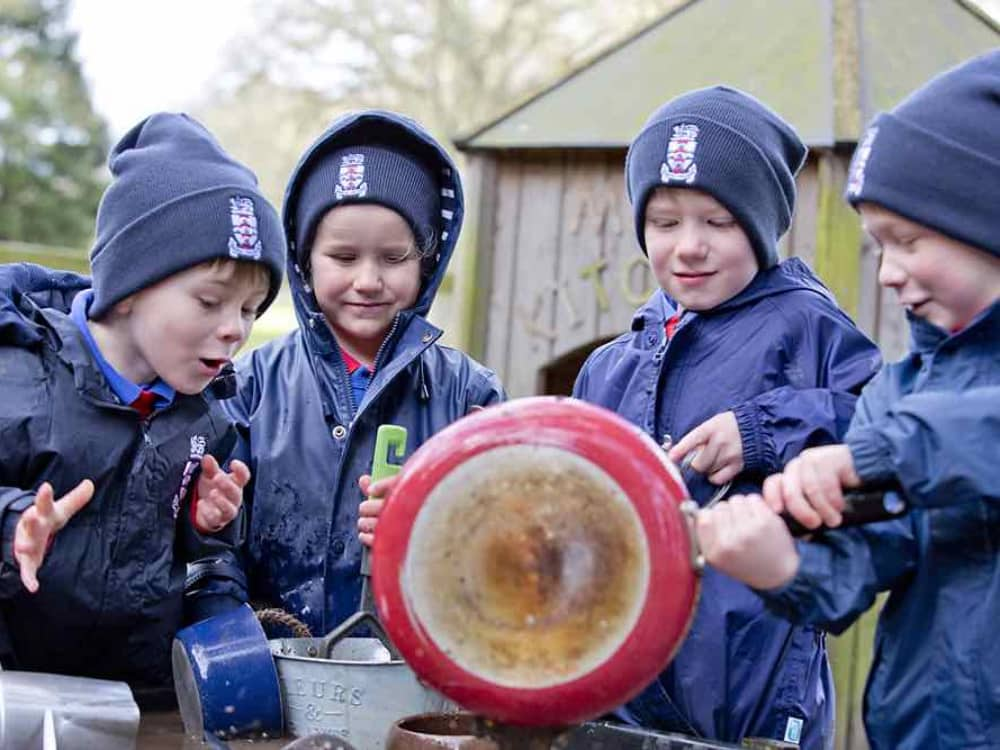 Pr-prep kids at Cheam School in their wet and warm outdoor clothing playing in the mud kitchen