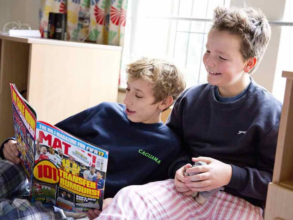 Two male Borders of Cheam School near Newbury relaxing in their dorms reading Match football magazine