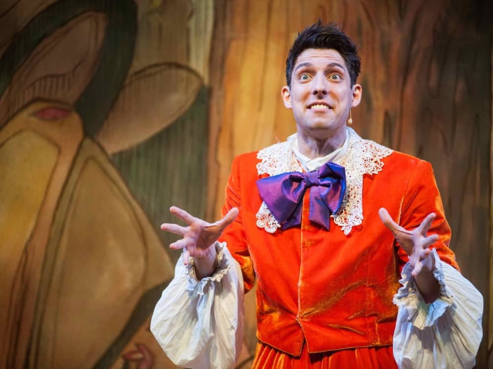 Village idiot Cuthbert wear Orange top and pants with a purple bow in Beautu and the Beast panto at the Corn Exchange Newbury