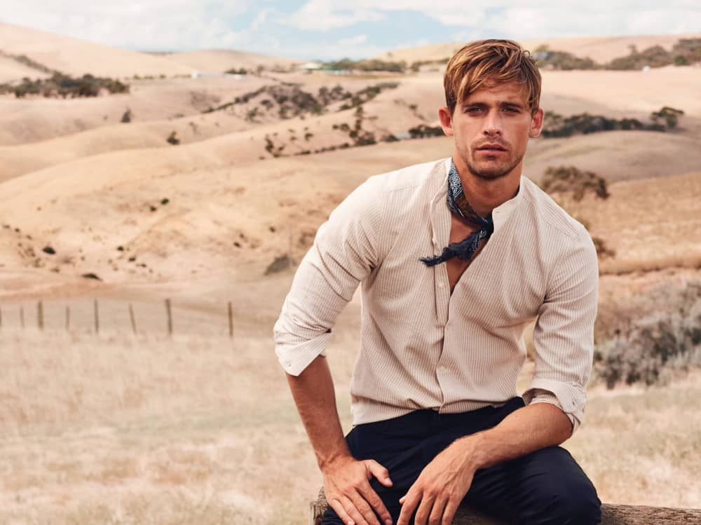 Ruffled dirty blonde hair of male model perched on a log in the Outback – Kevin Murphy