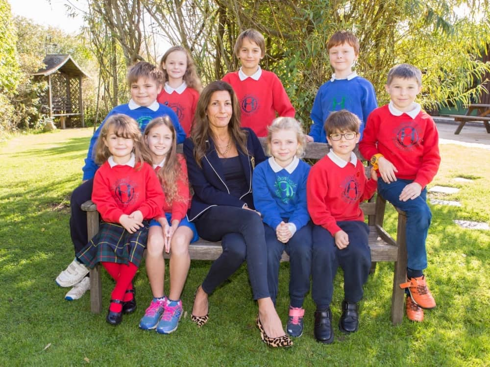 Meadow brook Montessori Director of Education Serena Gunn sits on a bench with the pupils in the grounds of the Berkshire school