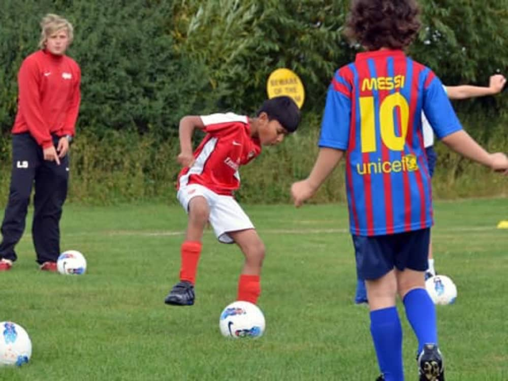 boys in Arsenal and Barcelona football kits battle it out on the football pitch at Meadowbrook Montessori in Warfield, Berkshire