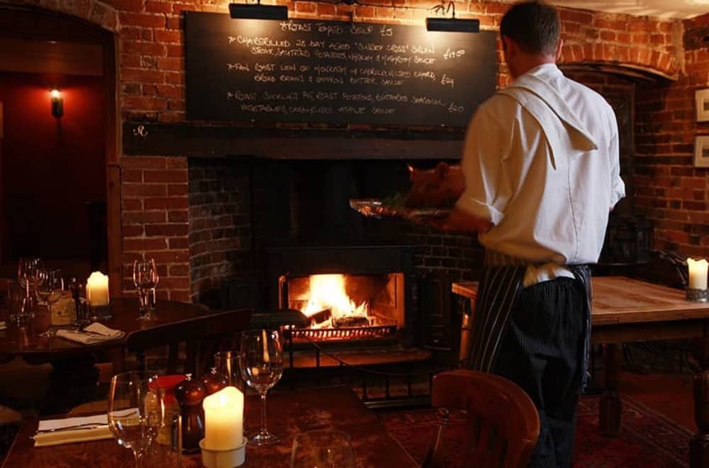 Roaring wood burning fire and well worn oak tables in the cosy country pun The Royal Oak Yattendon, West Berkshire
