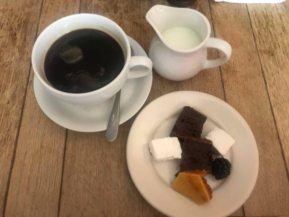 Coffee, milk and petit fours served in classic white china at the country pub Royal Oak in Yattendon Berkshire