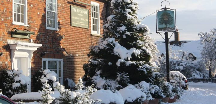 Show covered christmas tree outside the historic Royal Oak pub in Yattendon, Berkshire.