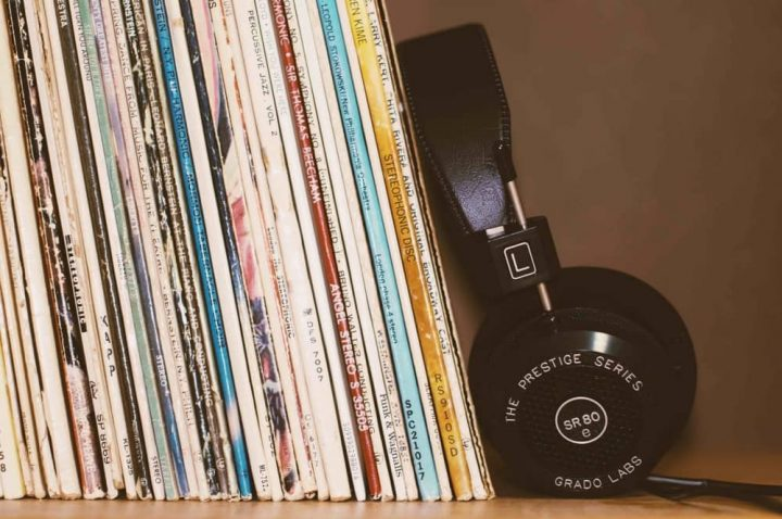 stack of vinyl albums stacked on shelf and headphones