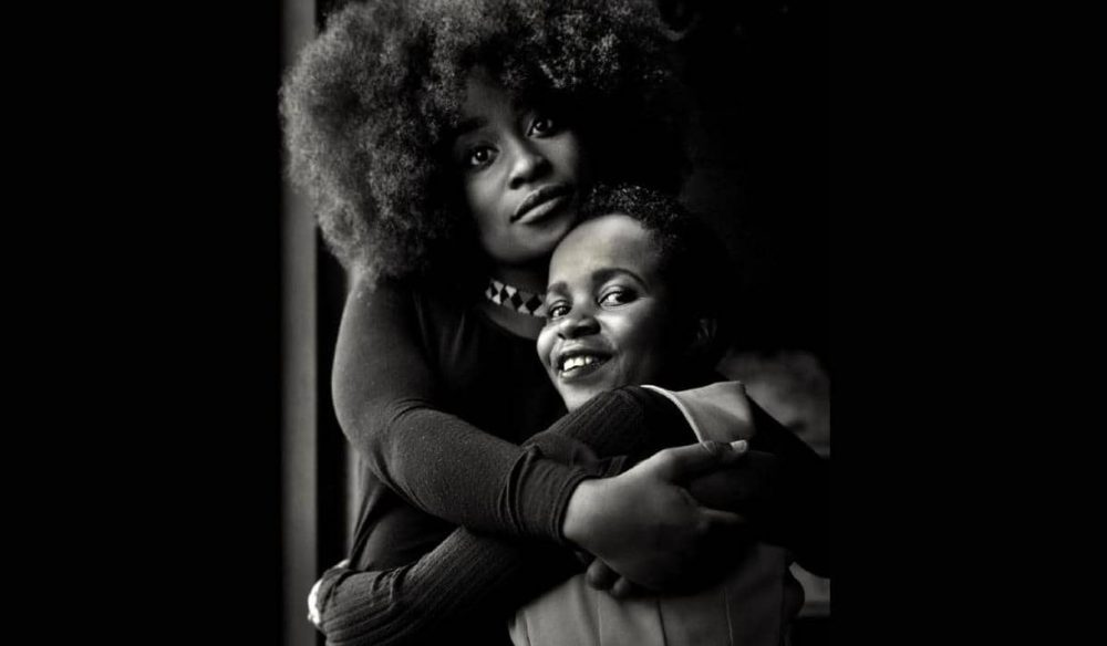Beautiful black woman with a big afro hug her smiling daughter