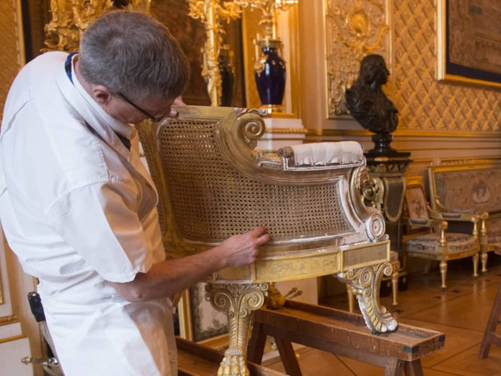 Windsor Castle conservationists restore the gilding on one of the antique chairs in the State Apartments