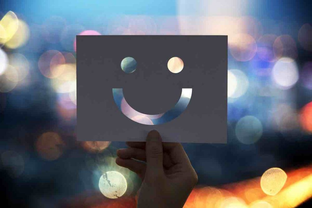 hand holding white card smiley face cut out blurry blue yellow lights background