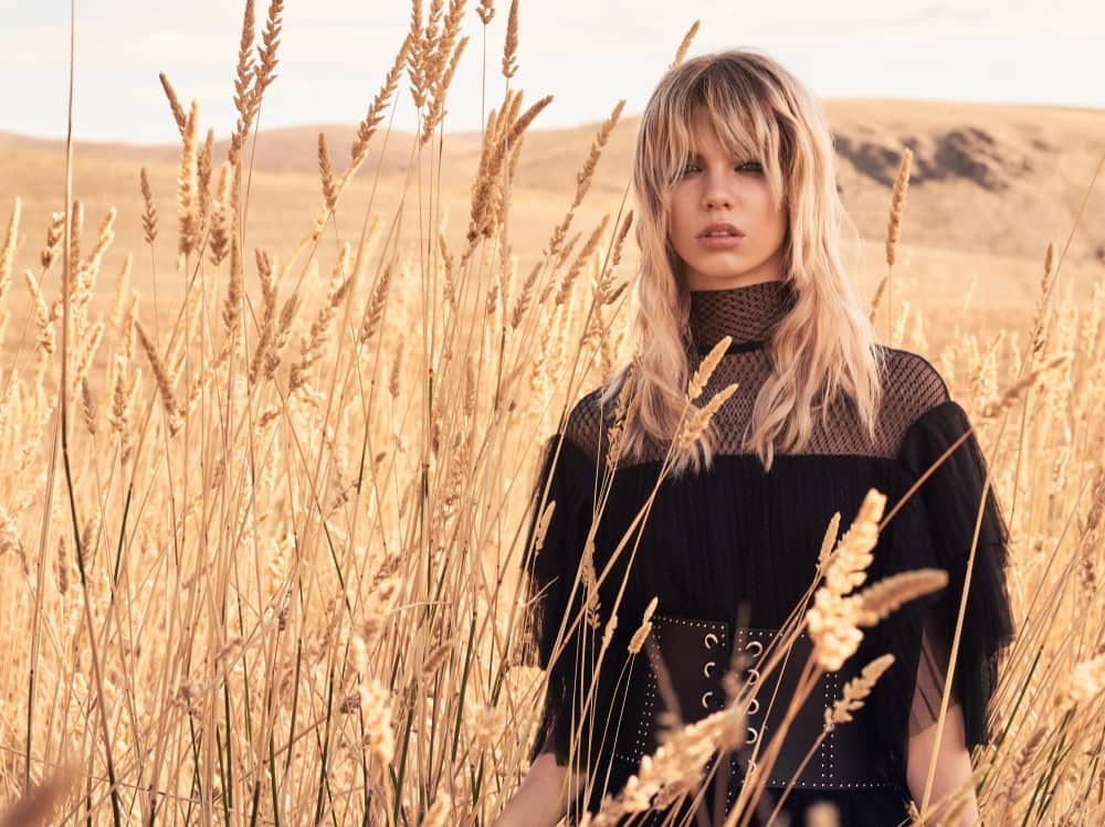 Long blonde hair and textured fringe on hair model in a corn field – Kevin Murphy