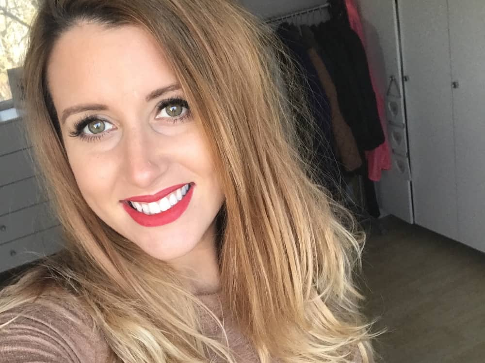 Jade Jones of The Art of Beauty with her signature red lip and beautiful blonde highlighted hair