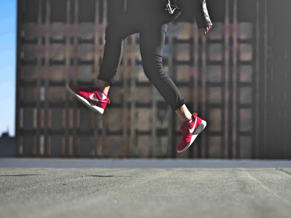 Energetic leap in red trainers