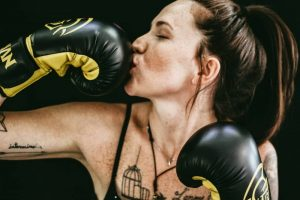 Woman with tattoos wearing boxing