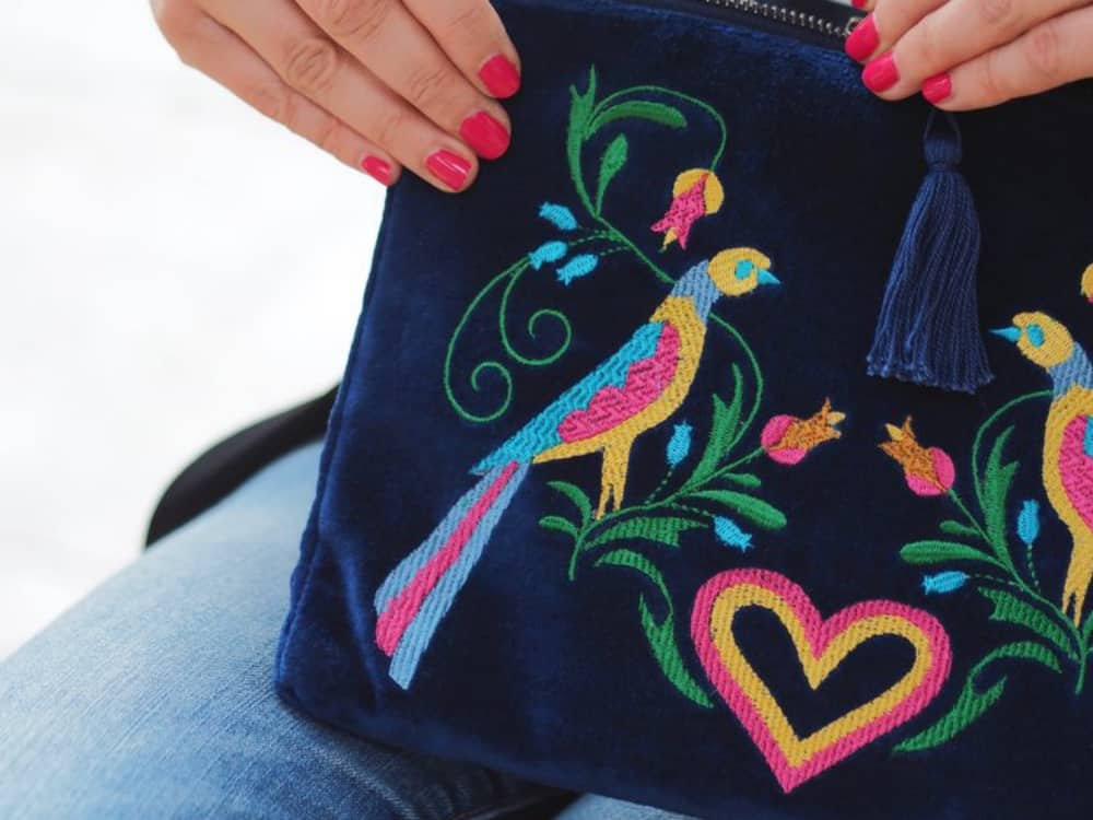 Navy blue velvet GiftPop clutch with yellow pink and green embroidered peacocks