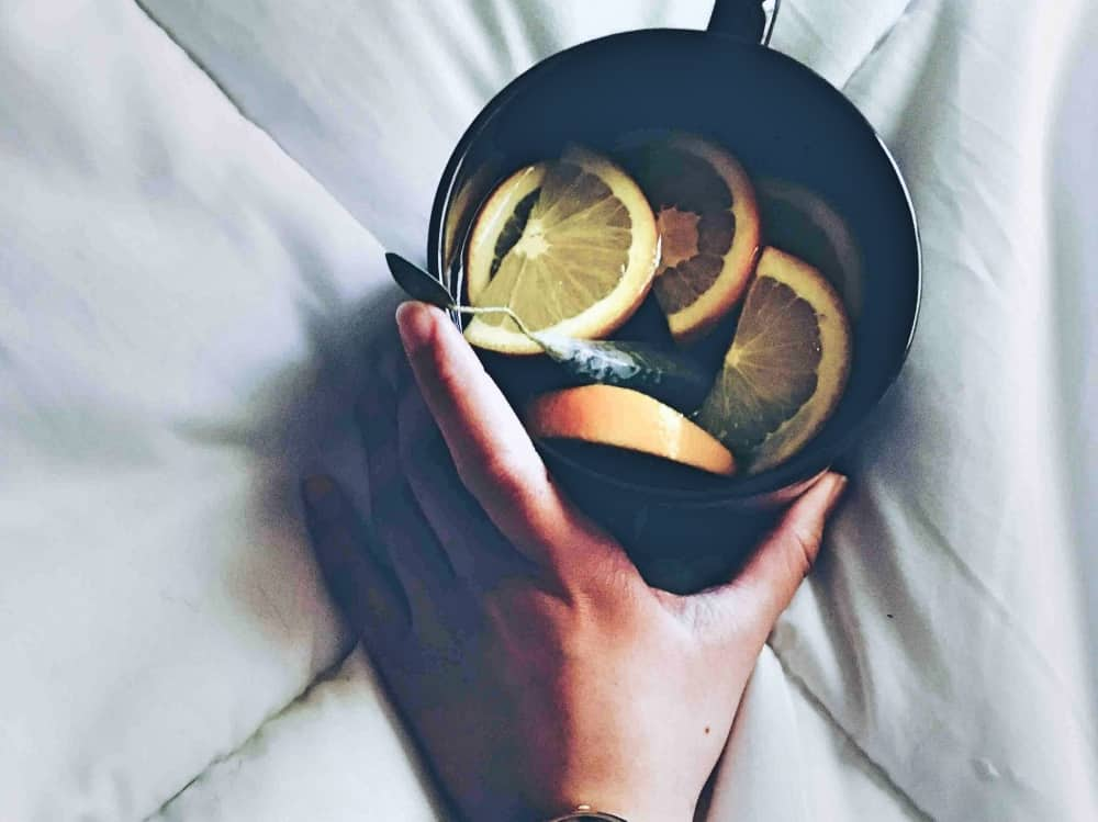 Hot water and fresh lemon in a black cup to help when you are sick