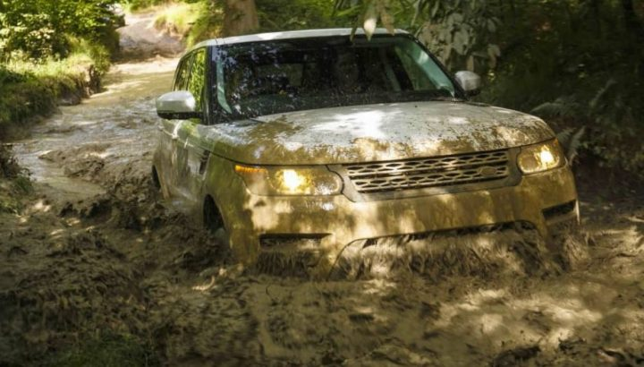 Land Rover driving off road through a massive muddy puddle