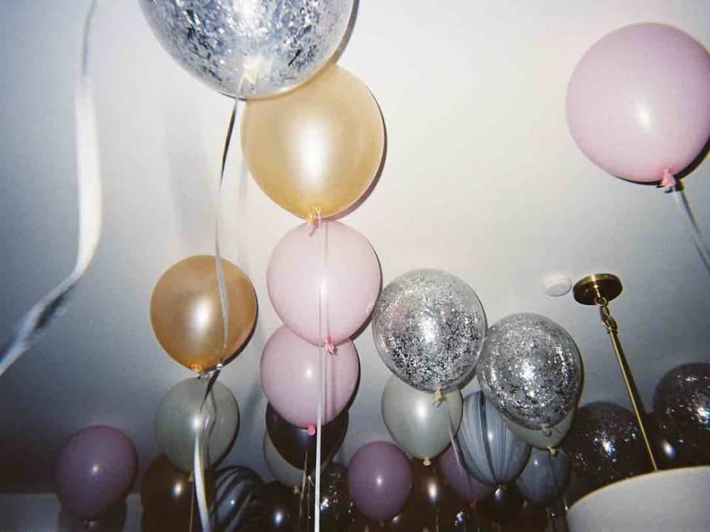silver, pink, gold helium balloons float to the ceiling