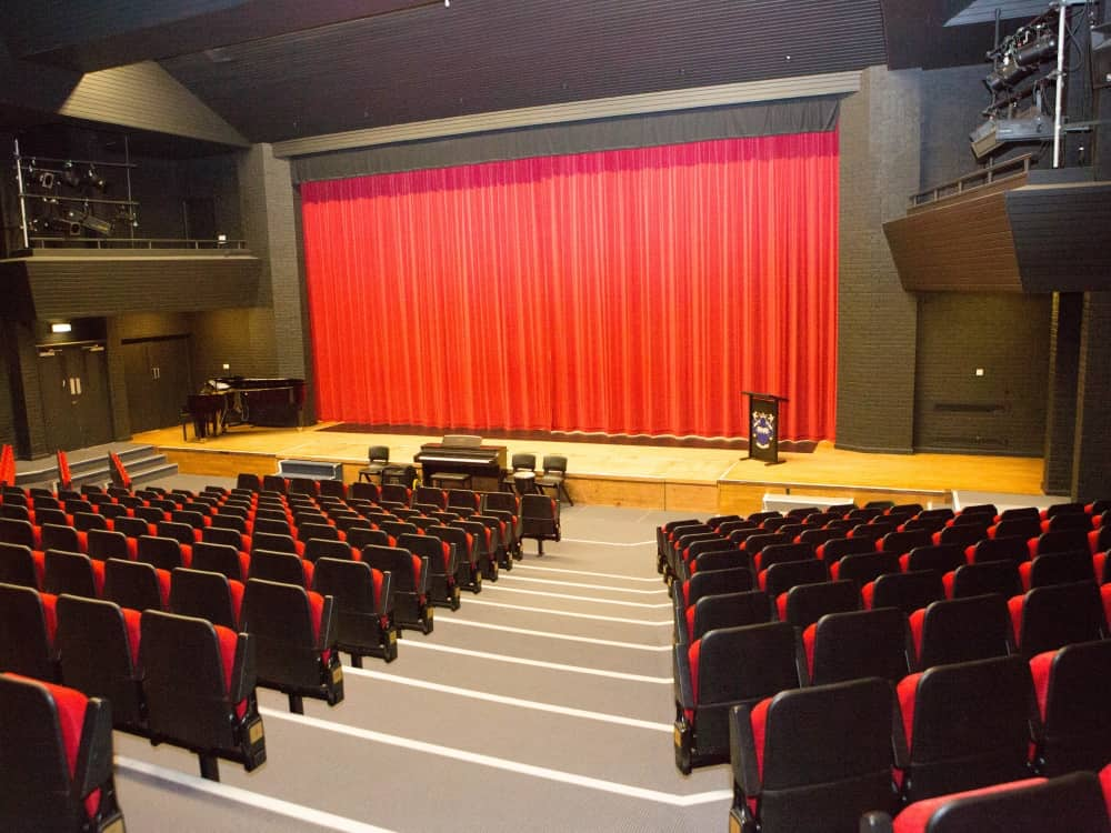 Bright red curtain across the large stage in the 350-seater theatre at Reddam House School Berkshire