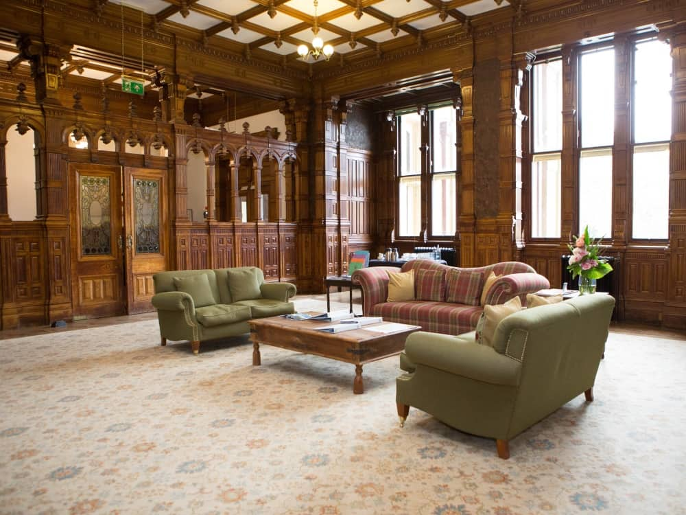 Comfy green and plaid sofas in the ornate wood panelled reception room at Reddham House Berkshire School