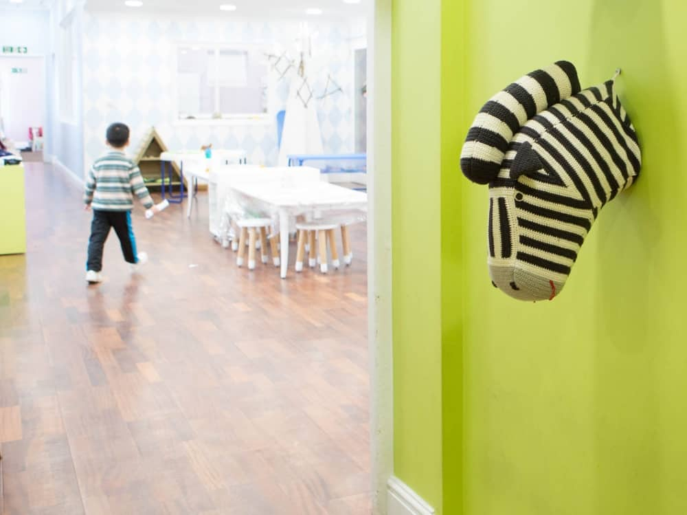 Soft toy animal head of a zebra pops out of lime green walls in the light, bright and big Early Learning classroom at Reddam House Berkshire School