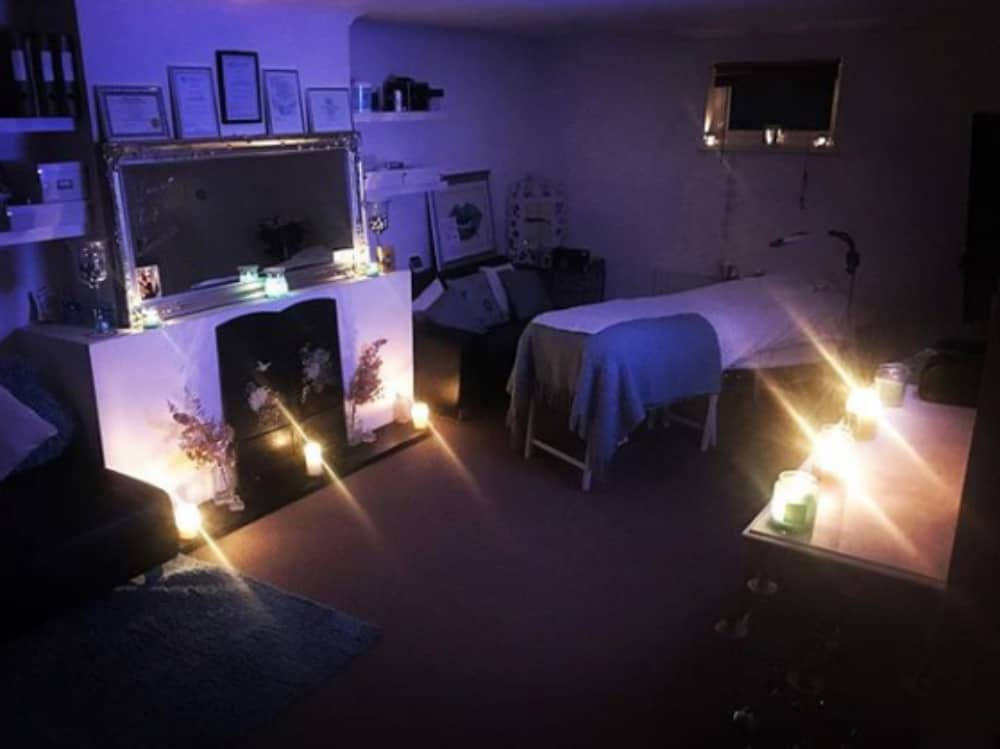 Large, candlelit beauty treatment room at The Art Of Beauty by Jade