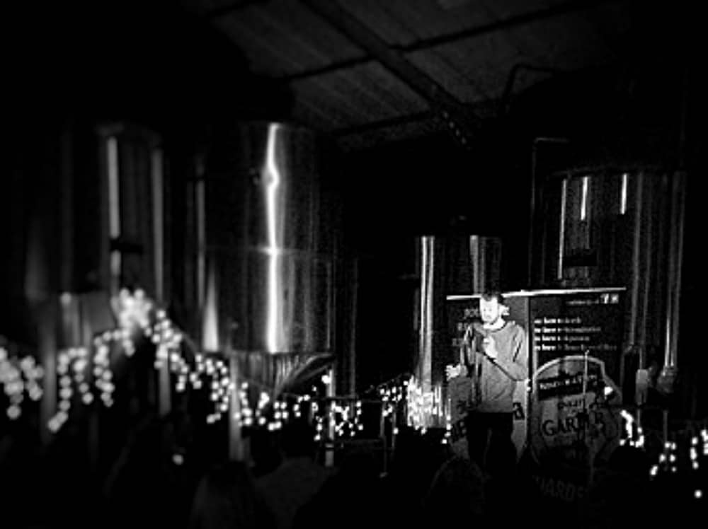 black white picture of comedian performing on the factory floor stage at Eton and Windsor Brewery