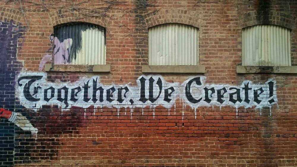 red brick building with Together We Create urban art