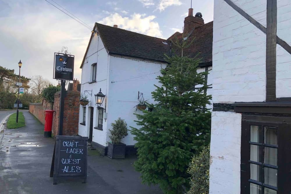 White and black exterior of Crown Bray heston Blumenthal pub and Christmas tree