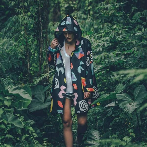 BLACK AND GRAPHIC PRINT RAIN MAC ON WOMAN IN A RAIN FOREST