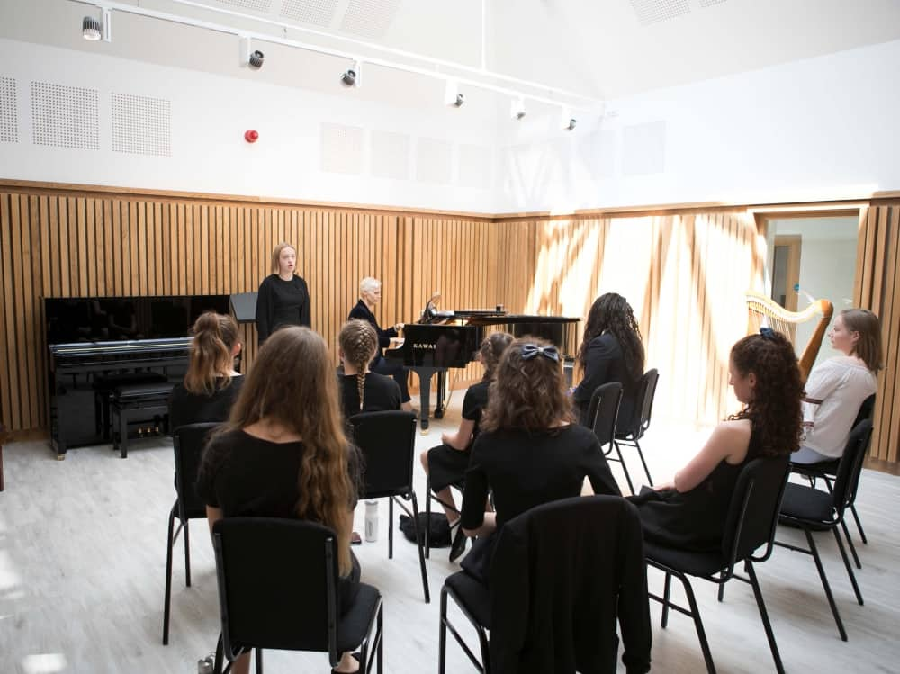 Queen Anne's School Ceversham Reading Berkshire Scott Music Centre white ceiling and slim wooden panels children performing on new black pianos
