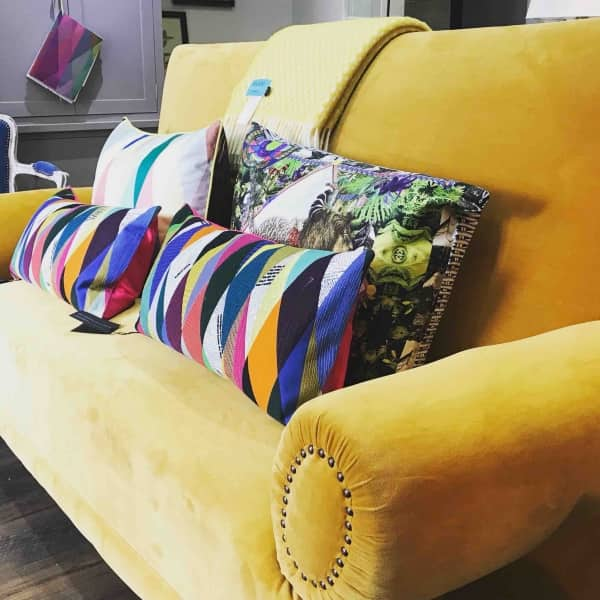 bright yellow velvet sofa with multi coloured harlequin oblong cushions and square floral cushion