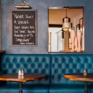 Dolphin Pub Newbury Berkshire Dark blue walls Teal leather banquette wooden tables blackboard with quote and stocking shop display Berkshire tights